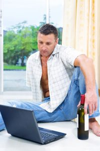 Man with a bottle of wine sitting in front of a laptop